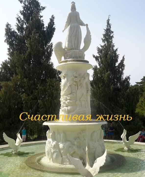 Красивый фонтан со статуей и лебедями