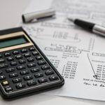 Калькулятор, ручка и расчеты на столе