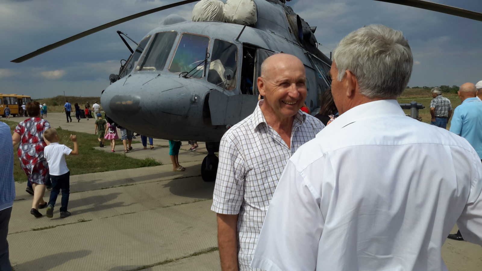 Однополчане беседуют на фоне вертолета