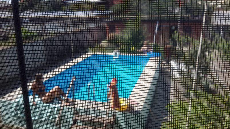 Женщина загорает у бассейна